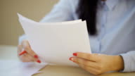 Close up woman hands writing filling in paper sheets inside office video