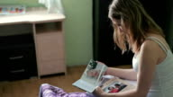 Close up Young Woman Looking At Photobook in bedroom video