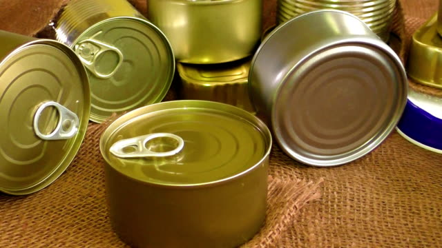 Closed metal tin cans on brown background video