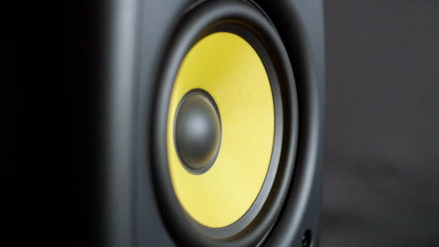 Close-up at moving big yellow diffuser. Sub-woofer. Speaker sub-woofer vibrates from loud music. Slow motion video