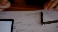 Close-up Attractive young female architect working at desk with plans on blueprint using the compass and enter the data into an electronic tablet video