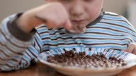 close-up. boy eatting flakes with milk at home video