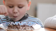 close-up. boys eatting flakes with milk at home video