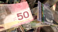 Close-up, Canadian Currency Flying Through a Warm Light (Loop) video