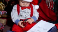 Closeup, child sitting under the tree with a letter to santa video