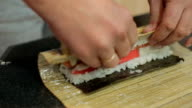 Close-up cook's hands making sushi roll video