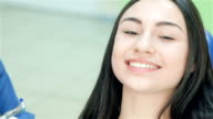 Close-up face of a girl who looks at the dentist and then teeth smile video