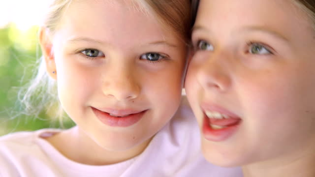 Closeup faces girls kiss on cheek with two affectionate sisters video