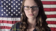 Close-Up Female with American Flag Raises Assault Rifle in Slow Motion video