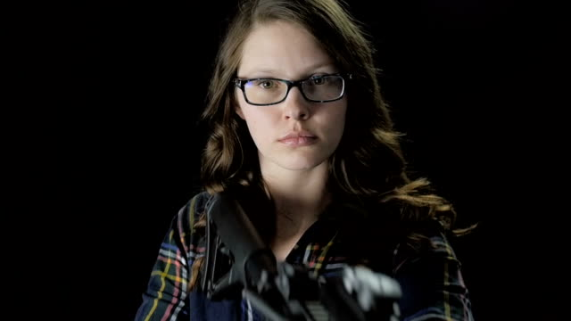 Close-Up Female with Glasses Raises Assault Rifle in Slow Motion video