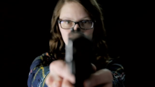 Close-Up Female with Glasses Raises Handgun in Slow Motion video