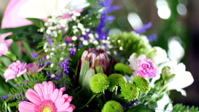 close-up, Flower bouquet in the rays of light, rotation, the floral composition consists of Chrysanthemum anastasis, gypsophila, solidago, Barbatus, Protea, Carnation, gerbera video