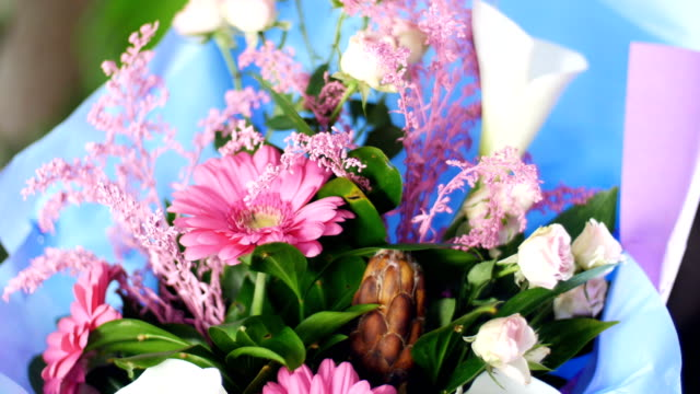 close-up, Flower bouquet in the rays of light, rotation, the floral composition consists of pink gerbera, Protea, calla, Rose yana creamy, solidago Russus video