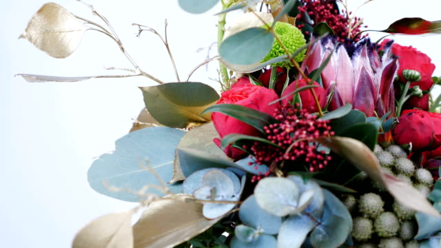 close-up, Flowers, bouquet, rotation on white background, consists of Protea, Brunia green, Barbatus, Rose pion-shaped bordeaux, pistachio tree, Ornithogalum, eucalyptus, Santini video