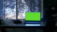 Close-up Footage of a Laptop with Green Mock-up Screen Standing on a Wooden Table. In the Background Big City Window View. video