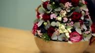Closeup fresh flower arrangement in a steel design bowl rotating video