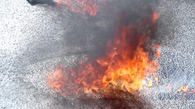 Closeup gasoline puddle on fire, burning liquid, accident, crash video