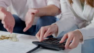 Closeup hands with calculator, husband wife plan family budget video