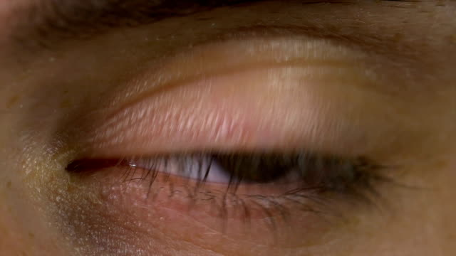 Closeup macro of young man eye blinking and looking around video