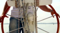 Closeup male captain steering boat on river, sailing, yachting video