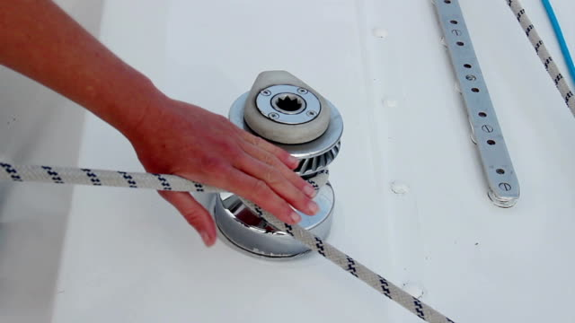 Closeup male hands securing rope on yacht, preparing to sail video
