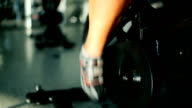 Close-up - man scrolls the pedals on the exercise bike in the gym video