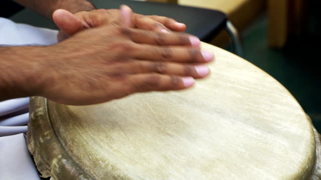 Closeup man's hands drumming out beat on skin-covered bongo hand drum. SLOW MO 1 video