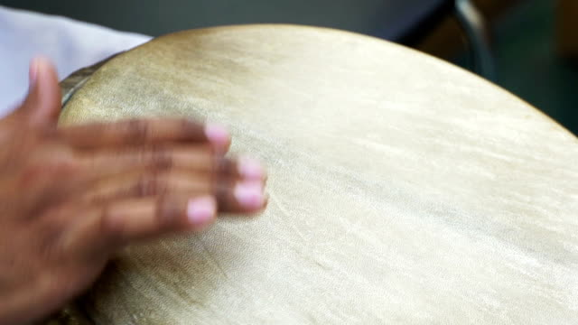 Closeup man's hands drumming out beat on skin-covered bongo hand drum. SLOW MO 3 video