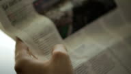close-up, modern man reading a French newspaper in the morning in his new office video