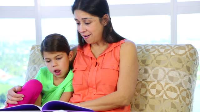 Closeup mother daughter reading video
