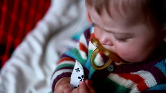 Close-up of a baby playing with playing cards in her crib video