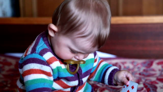 Close-up of a baby playing with playing cards on the bed video