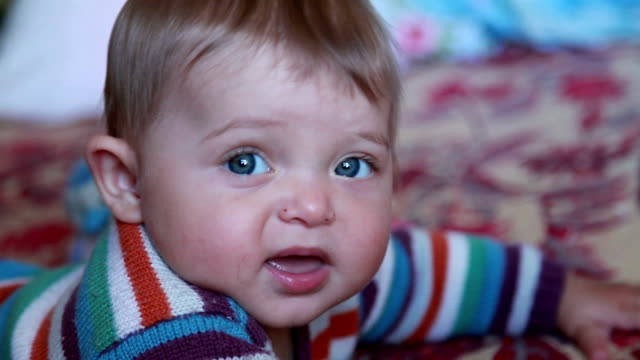 Close-up of a baby with open mouth looking at camera video