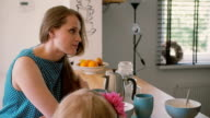 A close-up of a beautiful young mother and her daughter who is colouring at the kitchen table. Slow mo, Steadicam shot video