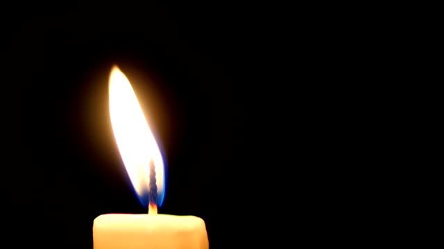 Close-up of a candle flame on black background. Loop. video