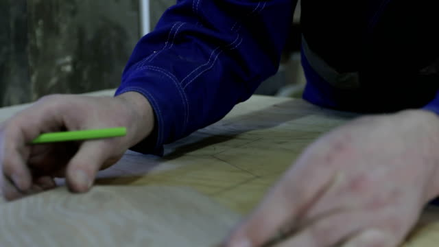 4K Close-up of a carpenter's hand outline a piece of furniture on a large board. video