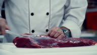 Close-up of a chef cut up the meat. The knife in the hands of the chef video