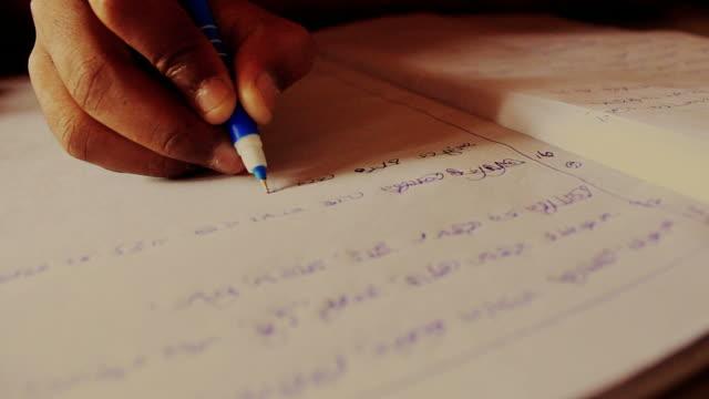 Closeup of a childs hand writing Bengali video