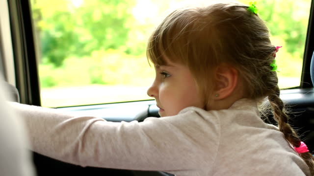 Close-up of a cute girl sitting in the car seat. video