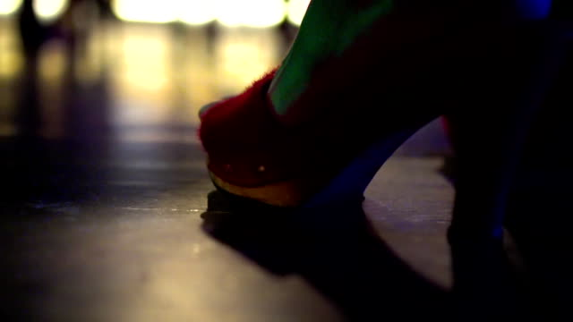 Close-up of a female foot in red high-heel shoe in a nightclub. video