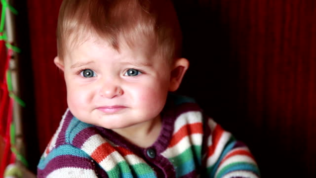 Close-up of a frowning baby sitting in the crib video