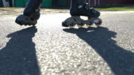 Close-up of a girl at sunset on roller skates. Slow motion video