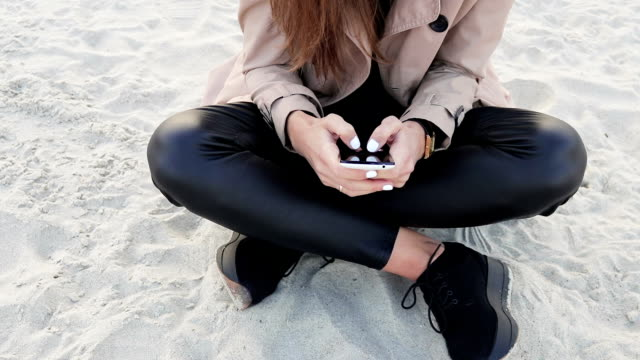 Close-up of a girl in a coat with a phone at the beach. Woman in black trousers and a beige coat sitting on the sand. video