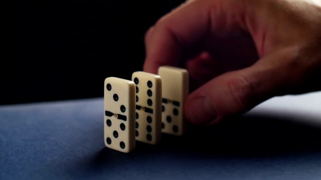 Closeup of a hand putting a domino. Dominoes falling. Nervous and failure video