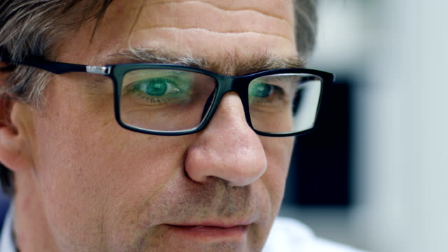 Close-up of a Male Senior Doctor Working at His Desk on a Personal Computer. Reflection of the Screen Seen in His Glasses. video