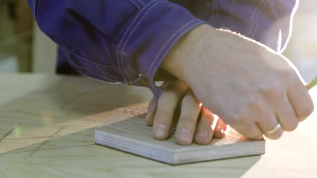 4K Close-up of a man's hands draw a piece of furniture on a board. Joiner marks out a large sheet of plywood. video