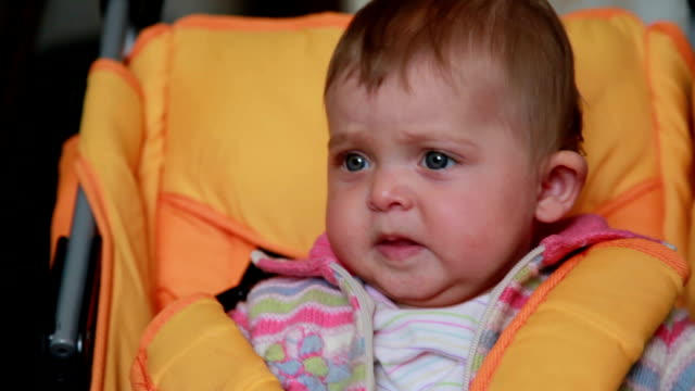 Close-up of a sad baby sitting in the pram video