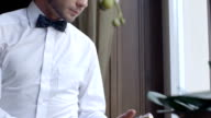 Closeup of a waiter in white shirt and bow tie presenting a champagne bottle video