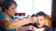 close-up of a woman feeding the boy lunch, delicious soup, happy family video