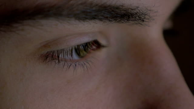Close-up of a young man eyes browsing on a tablet pc video